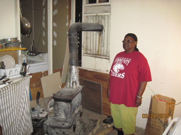 Winnie Williams beside the wood-burning stove that heated her home this winter.